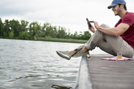 A man seated on a jetty by a lake, using a digital tablet. - MINF04927