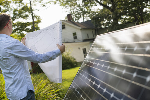 A man using a plan to place a solar panel in a farmhouse garden. - MINF04987
