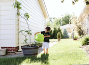 A boy, child standing in a garden watering a plant in a pot. - MINF05041