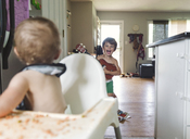 A baby girl sitting in a high chair covered in spilt food looking behind at a child, boy, brother and sister. - MINF05050