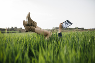 Woman lying on a field with legs in the air reading a book - JRFF01773