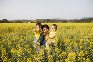 Spain, portrait of laughing mother with little son and daughter in a rape field - JRFF01782