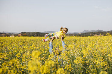 Spain, father and baby girl having fun  together in a rape field - JRFF01785