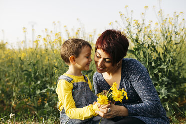 Mother and little son with picked flowers in a field - JRFF01788