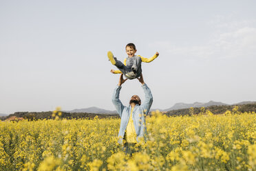 Spain, father and little son having fun  together in a rape field - JRFF01791
