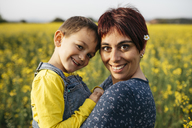 Portrait of mother and little son in a rape field - JRFF01797