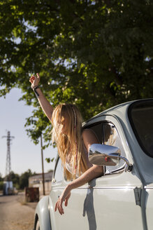 Happy young woman leaning out of car window - KKAF01350