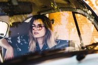 Young woman wearing sunglasses sitting in a car - KKAF01353