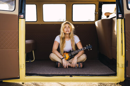 Young woman sitting in a van with a guitar - KKAF01368