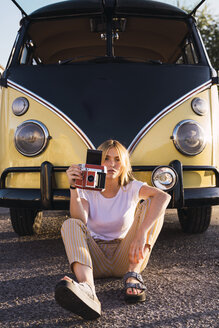 Young woman holding vintage camera sitting outside at a van - KKAF01374