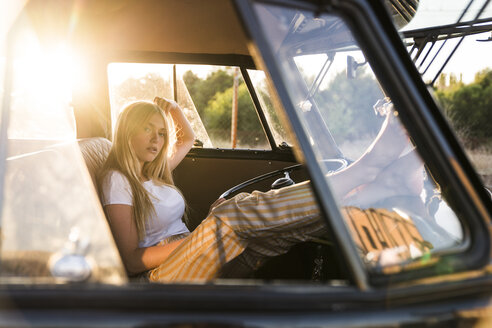 Portrait of young woman sitting in a van with feet up - KKAF01389