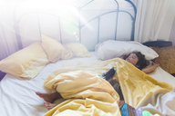 A young boy sleeping stretched out across a double bed. - MINF05083