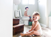 Baby girl sitting on floor of bathroom, and boy, child sitting on toilet, brother and sister. - MINF05107