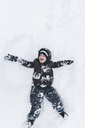 Boy, child lying and playing in snow. - MINF05128