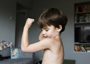 Boy, child flexing arm muscles in a living room. - MINF05143