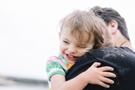 Close up of man with brown hair hugging smiling young girl. - MINF05208