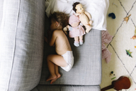 High angle view of young girl wearing nappy lying on her side on a sofa, sleeping. - MINF05232