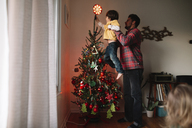 Man holding aloft young boy decorating illuminated Christmas Tree. - MINF05244