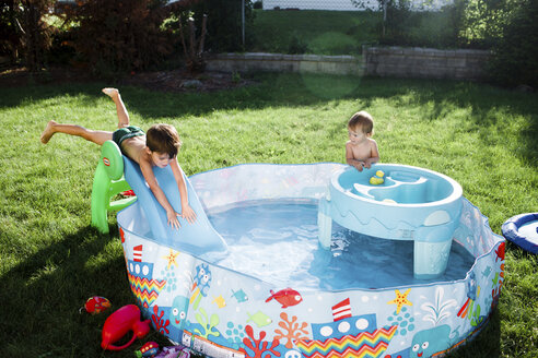 Boy, child, and baby girl playing in a paddling pool. - MINF05256