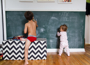 Boy, child, and toddler, girl drawing on blackboard with chalks. - MINF05259