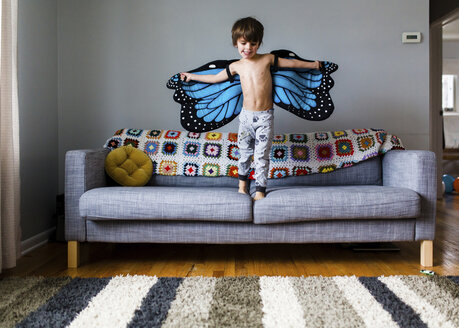 Young bare chested boy with brown hair wearing butterfly wings standing on a sofa. - MINF05286