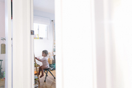 View thorough open door into nursery, young girl sitting on a chair at an easel, drawing. - MINF05289
