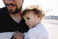 Smiling bearded man holding young girl, standing on a sandy beach by the ocean. - MINF05292