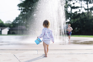 Rear view of young girl standing at a water fountain, holding blue bucket. - MINF05304