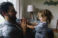 Smiling bearded man and young girl sitting on a sofa, playing. - MINF05307