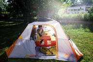 Young boy and girl sitting in a tent pitched on a lawn in a garden. - MINF05316