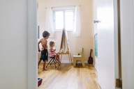 View through an open door into a nursery, boy and girl  at an easel, drawing. - MINF05319