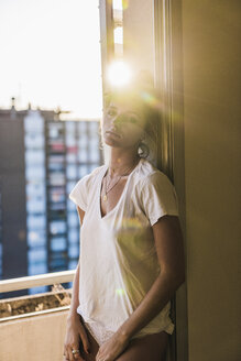 Portrait of young woman standing at the window in backlight - KKAF01423