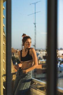 Young woman wearing bra standing on balcony - KKAF01429