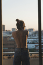 Rear view of topless young woman standing on balcony - KKAF01438