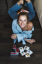Portrait of happy young woman lying on the floor with instant photos of herself - KKAF01447