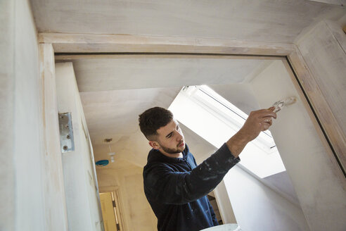 A builder, painter holding a paint brush, painting a door frame. - MINF05461
