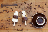 homemade Espresso Macchiato ice lollies with cup of Espresso and coffee beans on wooden background - GWF05626