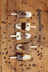 homemade Espresso Macchiato and Latte Macchiato ice lollies with coffee beans on wooden background - GWF05632