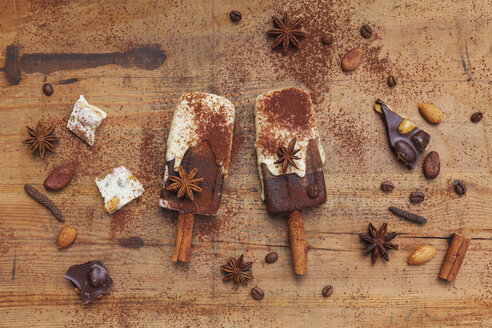 Homemade espresso and white chocolate ice lollies with winter spices on wooden background - GWF05638