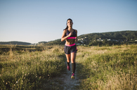 Sportswoman jogging on path - RAEF02062