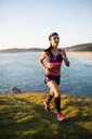 Young woman running on the coast - RAEF02068