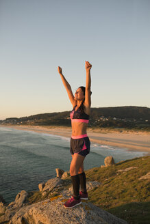 Sportive woman with arms raised in the sunset light - RAEF02071