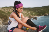 Sportive woman sitting on rocks in the evening - RAEF02083