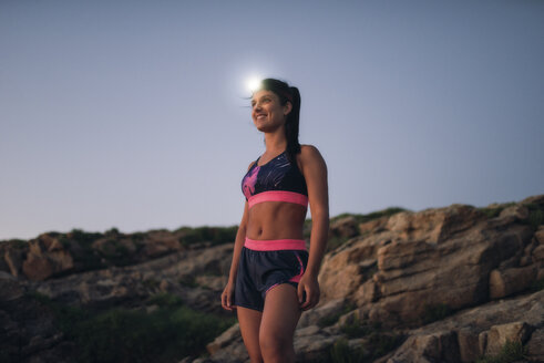 Sportive woman with headlamp standing on rocky coast - RAEF02092