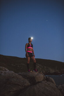 Sportive woman with headlamp standing on rocks in the evening - RAEF02095