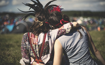 Rear view of two young women at a summer music festival wearing feather headdresses, arm around shoulder. - MINF05553