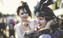 Two young women at a summer music festival faces painted, wearing feather headdress. - MINF05556