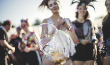 Revellers at a summer music festival large soap bubbles in foreground. - MINF05559