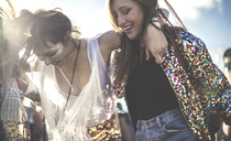 Two young women at a summer music festival wearing sequins with painted faces laughing and dancing. - MINF05562