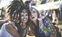 Three young women at a summer music festival wearing feather headdress and faces painted, smiling at camera. - MINF05565